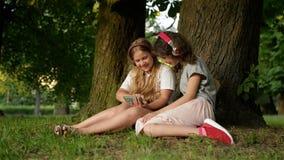 Dos hermanas jovenes lindas con los auriculares que se divierten en día hermoso Niños felices que juegan en parque del verano Obs metrajes