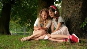 Dos hermanas jovenes lindas con los auriculares que se divierten en día hermoso Niños felices que juegan en parque del verano Obs almacen de metraje de vídeo