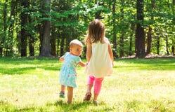 Dos hermanas jovenes que llevan a cabo las manos afuera Fotos de archivo libres de regalías