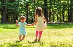 Dos hermanas jovenes que llevan a cabo las manos afuera Imagen de archivo