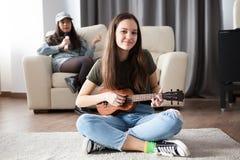 Dos hermanas, la más joven están tocando una pequeña guitarra en frente en el otra están cantando en la parte posterior Foto de archivo libre de regalías