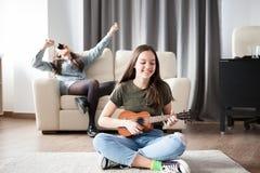 Dos hermanas, la más joven están tocando una pequeña guitarra en frente en el otra están cantando en la parte posterior Imagenes de archivo