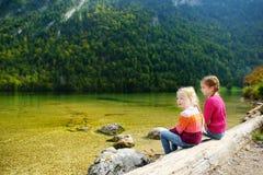 Dos hermanas lindas que disfrutan de la vista de las aguas de color verde oscuro de Konigssee, conocidas como el ` s de Alemania  Imagenes de archivo
