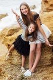 Dos hermanas lindas se están colocando en la playa Fotografía de archivo