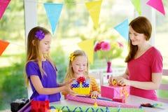 Dos hermanas lindas y su madre joven que envuelven los regalos en papel de embalaje colorido Imagen de archivo libre de regalías