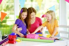 Dos hermanas lindas y su madre joven que envuelven los regalos en papel de embalaje colorido Imágenes de archivo libres de regalías