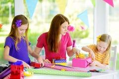 Dos hermanas lindas y su madre joven que envuelven los regalos en papel de embalaje colorido Fotos de archivo