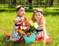 Dos hermanas Muchachas adorables del pequeño niño con el ramo de flores en feliz cumpleaños Fotos de archivo libres de regalías