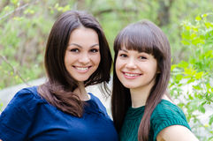 Dos hermanas o amigas que sonríen, riendo y abrazos al aire libre en primavera o verano Foto de archivo libre de regalías