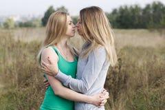 Dos hermanas o amigos femeninos en un abrazo cercano Imagenes de archivo