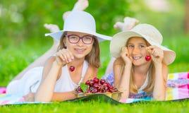 Dos hermanas o amigos lindos en un jardín de la comida campestre mienten en una cubierta y comen cerezas recientemente escogidas Foto de archivo