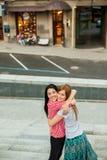 Dos hermanas que abrazan en la calle Fotografía de archivo libre de regalías