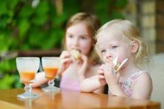Dos hermanas que beben el jugo y que comen los pasteles Imagen de archivo libre de regalías