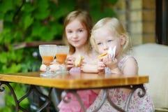 Dos hermanas que beben el jugo y que comen los pasteles Fotos de archivo
