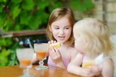 Dos hermanas que beben el jugo y que comen los pasteles Fotografía de archivo libre de regalías
