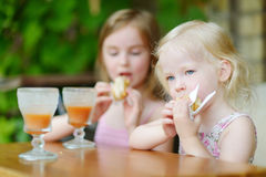 Dos hermanas que beben el jugo y que comen los pasteles Fotografía de archivo