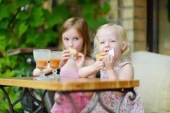 Dos hermanas que beben el jugo y que comen los pasteles Foto de archivo libre de regalías
