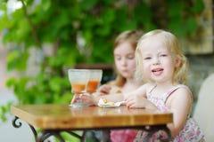 Dos hermanas que beben el jugo y que comen los pasteles Imagen de archivo