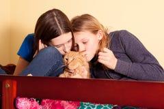 Dos hermanas que besan el gato Imagen de archivo libre de regalías