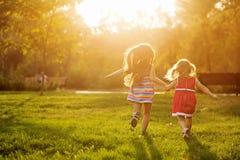 Dos hermanas que corren en el césped Imagenes de archivo
