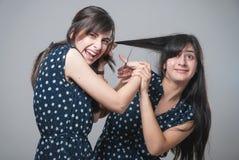 Dos hermanas que cortan su pelo con las caras divertidas Imagen de archivo libre de regalías