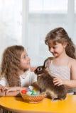 dos hermanas que juegan con el conejito de pascua Imagen de archivo libre de regalías