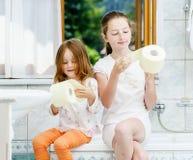 Dos hermanas que juegan con el rollo del papel higiénico Imágenes de archivo libres de regalías