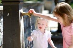 Dos hermanas que juegan con la fuente del agua potable fotografía de archivo