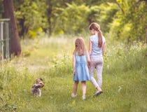 Dos hermanas que juegan con poco día soleado más terier de Yorkshire Imagen de archivo