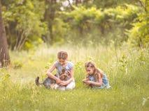 Dos hermanas que juegan con poco día soleado más terier de Yorkshire Foto de archivo