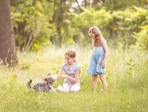 Dos hermanas que juegan con poco día soleado más terier de Yorkshire Fotos de archivo libres de regalías