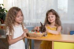 dos hermanas que juegan con un conejito de pascua Fotografía de archivo