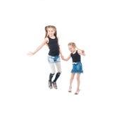 Dos hermanas que juegan, sonriendo y llevando a cabo las manos Imagenes de archivo