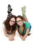 Dos hermanas que mienten en un suelo blanco Imagen de archivo libre de regalías