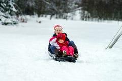 Dos hermanas que montan por día de invierno de los trineos Imagen de archivo libre de regalías