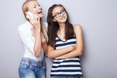 Dos hermanas que presentan con el teléfono móvil Imagen de archivo