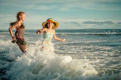 Dos hermanas que salpican en la playa Imagen de archivo libre de regalías