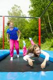 Dos hermanas que saltan en el trampolín fotografía de archivo