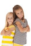 Dos hermanas que se colocan de nuevo a la parte posterior con los brazos doblados Imágenes de archivo libres de regalías