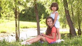 Dos hermanas que se divierten en el parque Cámara lenta almacen de metraje de vídeo
