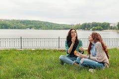 Dos hermanas que se divierten mientras que hace burbujas y siéntase en el g fotografía de archivo