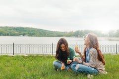 Dos hermanas que se divierten mientras que hace burbujas y siéntase en el g imágenes de archivo libres de regalías