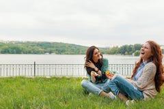 Dos hermanas que se divierten mientras que hace burbujas y siéntase en la hierba fotos de archivo