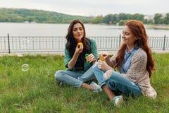 Dos hermanas que se divierten mientras que hace burbujas y siéntase en la hierba imagen de archivo libre de regalías