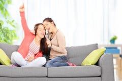 Dos hermanas que se divierten que canta en el micrófono Foto de archivo