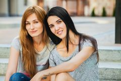 Dos hermanas que se sientan en las escaleras y la música que escucha Imágenes de archivo libres de regalías
