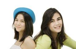 Dos hermanas que se sientan junto, aislado en blanco Fotos de archivo libres de regalías