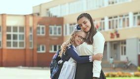 Dos hermanas rusas de las colegialas que presentan en ropa festiva en el día del principio del año escolar almacen de metraje de vídeo