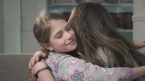 Dos hermanas se abrazan cercano para arriba Muchachas más pequeñas y más viejas frotan sus narices y sonrisa Relación de las herm almacen de video
