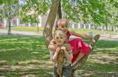 Dos hermanas se divierten en un paseo en un día de verano caliente en el parque imagen de archivo